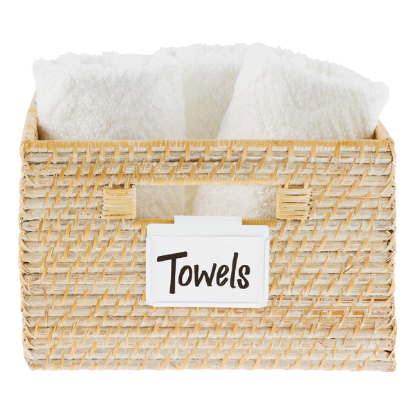 A close up of a basket filled with white towels. Label on basket says Towels